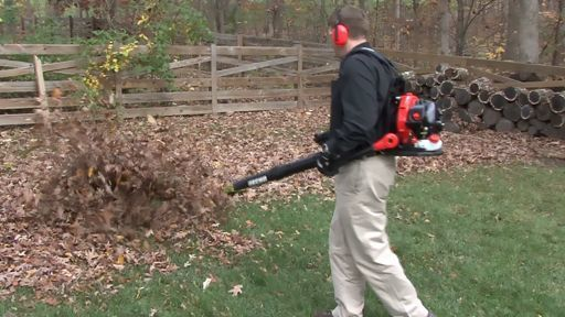 Battery Powered Leaf Blower Reviews man blowing leaves in a big backyard