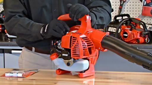 Battery Powered Leaf Blower Reviews Maintenance being performed with a man with black gloves