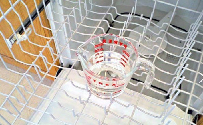 Glass measuring cup filled with white vinegar placed  in the dishwasher top rack
