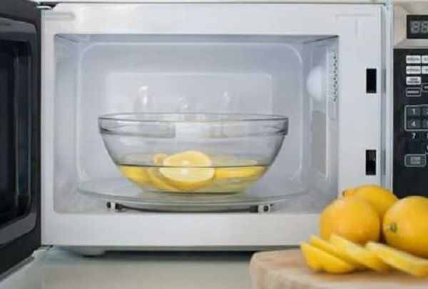 Simple Hacks to Clean Your House - Bowl half-full of white vinegar and lemon slices inside an open microwave with lemon slices on top of a wooden table in front of the microwave