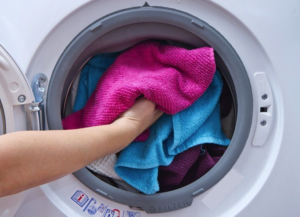 Towels being put inside a dryer