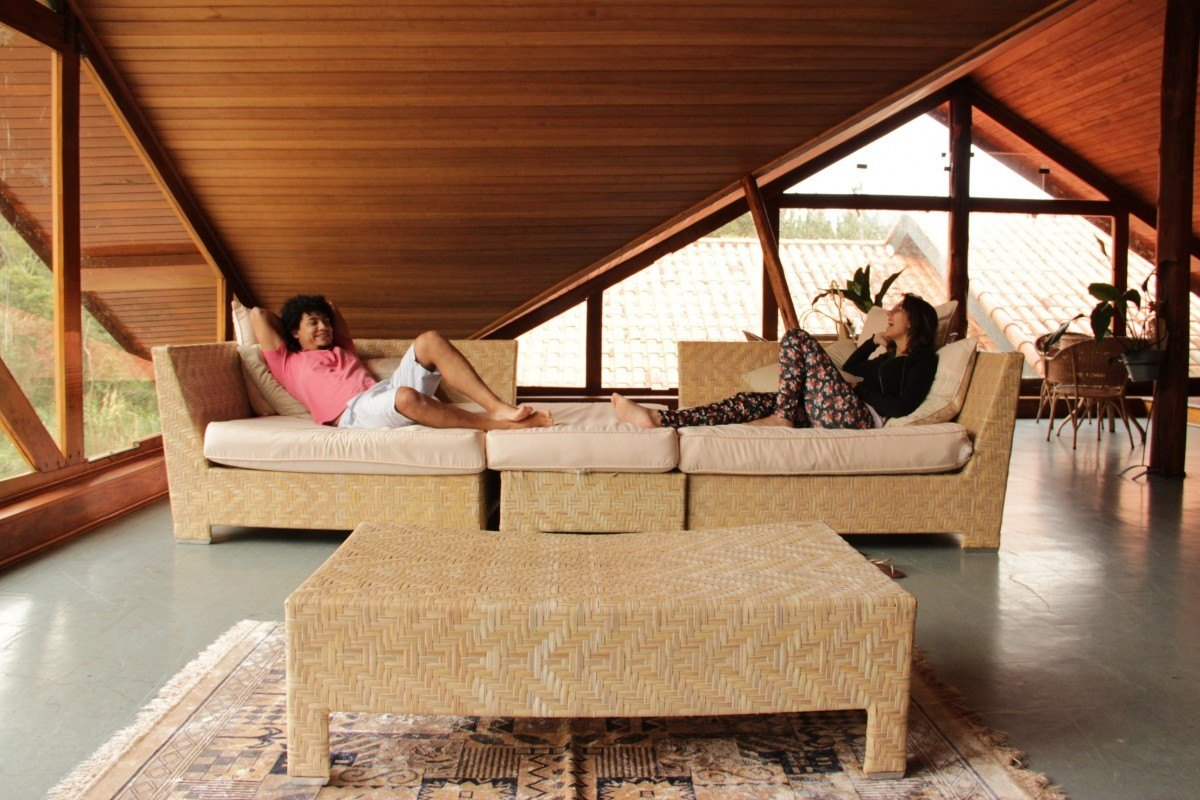 two people lounging on a very clean, well lit, and comfortable attic living room