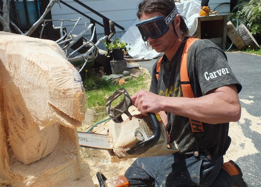 a man carving with a chainsaw